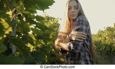 Charming girl with long hair posing next to a vineyard in...