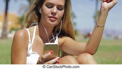 Charming girl with phone and headphones - Young beautiful...