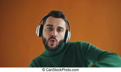 Charming guy listening to music in headphones dancing sending air kisses
