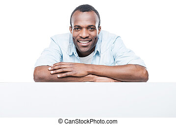 Charming handsome. Handsome African man in blue shirt leaning at copy space and smiling while standing against white background