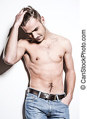 Charming handsome. Handsome young shirtless man in jeans holding hand in hair while