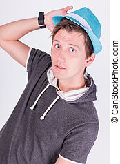 Charming handsome young man in formalwear Holds a blue hat white background
