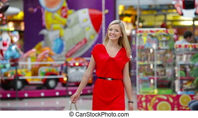 Beautiful young woman in red carrying shopping-bags after a spree