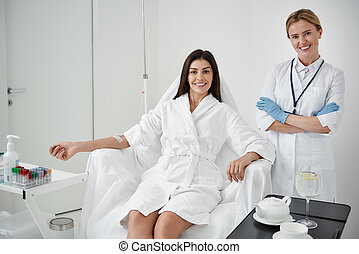Charming lady receiving IV infusion while doctor crossing arms