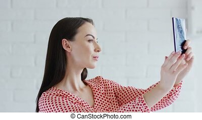 Charming lady taking selfie - Side view of lovely young...