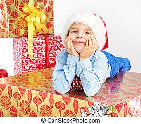 Charming little boy lying on present