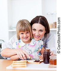 Charming little girl and her mother preparing toasts