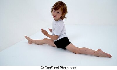 Charming little girl doing gymnastic exercises in the studio...
