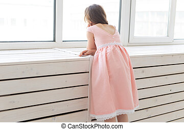 Charming little girl in a lush peach princess dress looks out the window of her room. The concept of children's desires and expectations of a miracle.