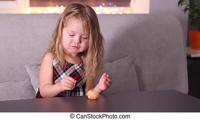 charming little girl in red checkered dress with mandarins Clementine in gray room. new year, childhood, christmas. Full HD footage.
