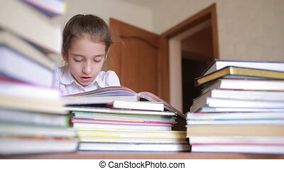 Charming little girl in school uniform is reading a book, sitting between piles of books