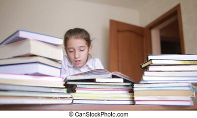 little girl in school uniform is reading a book, sitting between piles of books
