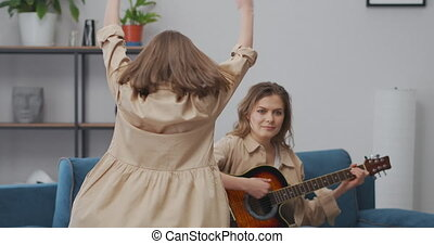 charming little girl is whirling and dancing in living room, adult woman is playing music on guitar, fun and entertainment