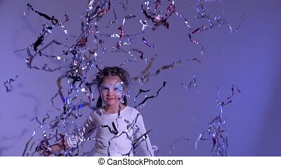 Charming little girl jumping and throwing up silver tinsel -...