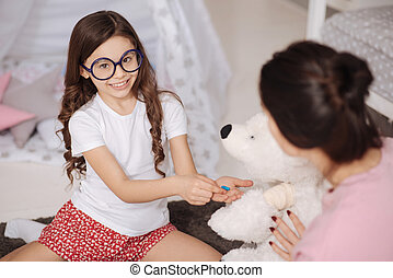 Charming little girl taking care of favorite toy at home