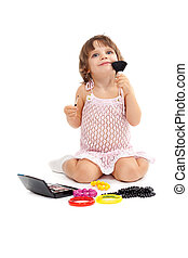 Charming little girl with makeup and colored beads in the studio sitting on the floor. Isolate on white.