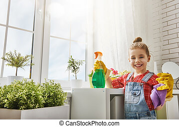 Charming little helper. Cute little child girl makes cleaning the house. Girl rubs dust.