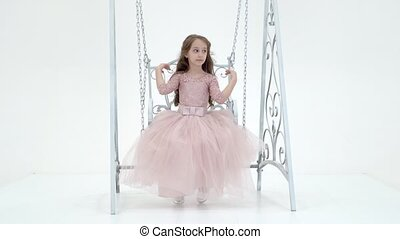 Portrait of a beautiful Preteen girl swinging on a gorgeous metal swing. Charming long-haired girl in a beautiful pink dress sits with her head bowed and looking at the camera in the studio