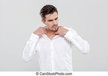 Charming man adjusting his shirt