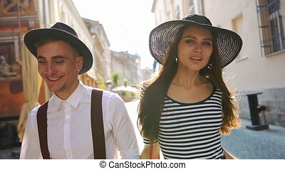 Charming man and woman in black hats run along the street on the sunset