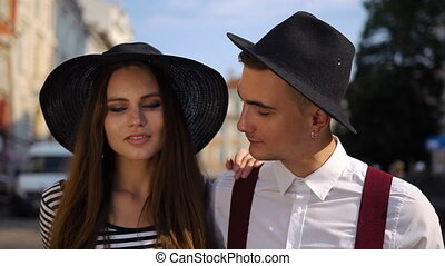 Charming man and woman in black hats walk along the street on the sunset