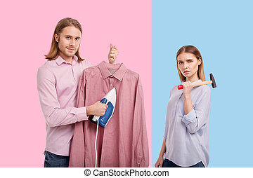 Charming man and woman posing while doing household chores