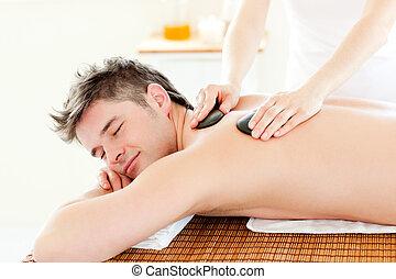 Charming man enjoying a massage with hot stone