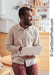 Charming man leaning on table and holding laptop
