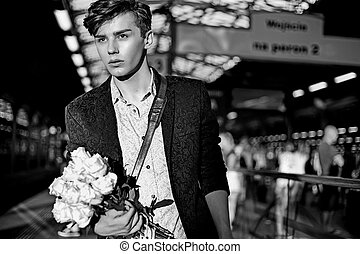 Charming man standing in the railway station