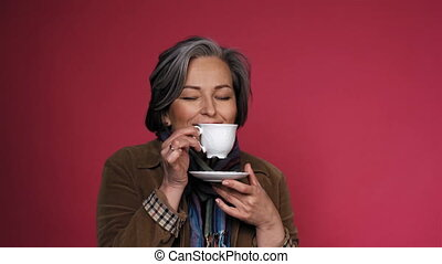 Charming mature woman enjoys cup of coffee with eyes closed. Happy gray-haired lady drinks coffee posing on pink background in the studio. Close up portrait with text space on right. Prores 422.