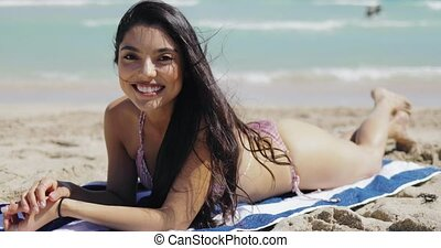 Charming model lying on beach smiling at camera