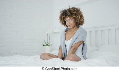 Charming model posing on bed - Young adorable ethnic woman...