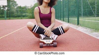 Charming model sitting on skateboard - Charming ethnic model...