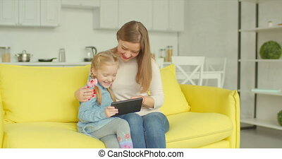 Charming mom and daughter working on tablet pc