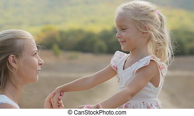 Charming mom with little daughter laughing and hugging in the middle of the field in slow motion