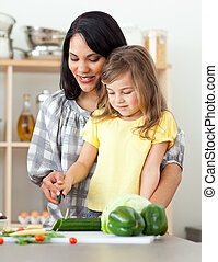 Charming mother helping her daughter prepare salad