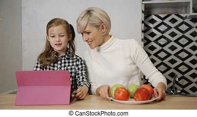 Charming mother is giving tasty and fresh apples to little...