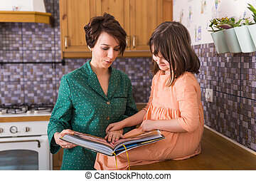 Charming mother is showing images in a book to her cute little daughter at home