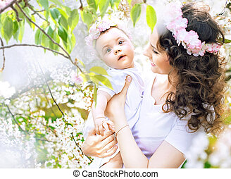 Charming mother walking in the orchard with a daughter