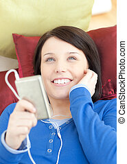 charming, mulher jovem, escutar, música, mentindo, ligado, um, sofá