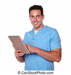 Charming nurse man using his tablet pc