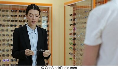 Charming optician selling glasses in optical shop -...