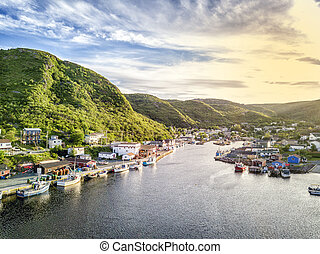 Charming Petty Harbour with green hills and wooden...