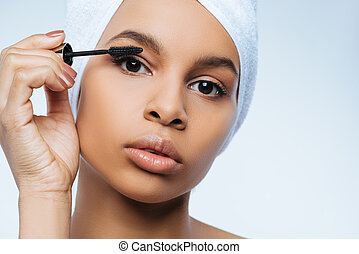 Charming pleasant woman putting on mascara