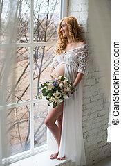 Charming pregnant girl looks out the window with a bouquet of flowers.