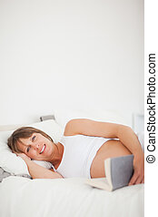 Charming pregnant woman reading a book while lying on her bed