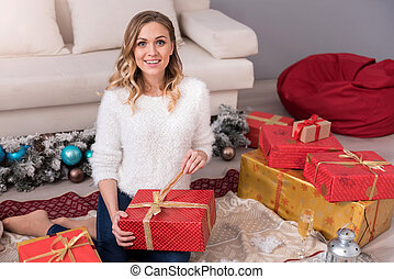 Charming pretty woman unpacking her gift