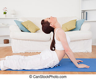 Charming red-haired female stretching in the living room
