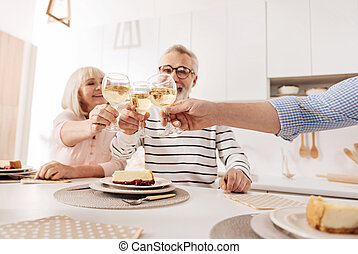 Charming retired couple enjoying dinner with son at home