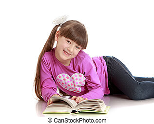 Charming schoolgirl reading a book lying on the floor